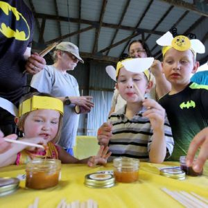 Young kids being supervised by parents during honey tasting contest.