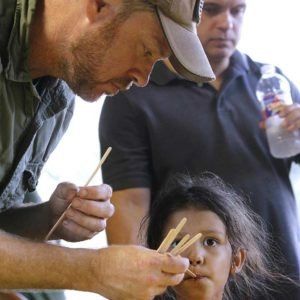 Father giving young daughter honey tasting samples.