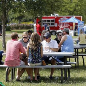 Visitors eating and relaxing at picnic tables.