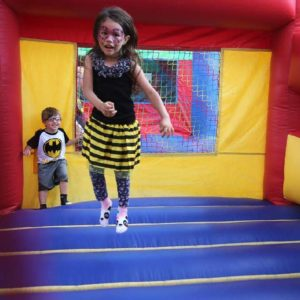 Little girl in bee costume jumping in bounce house.