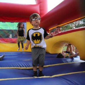 Young boy in batman shirt in bounce house.