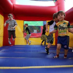 Young children jumping in bounce house.